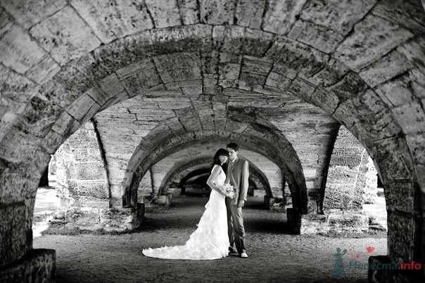 Жених и невеста стоят, прислонившись друг к другу, под каменной аркой - фото 55023 Свадебный распорядитель - Бедрикова Оксана