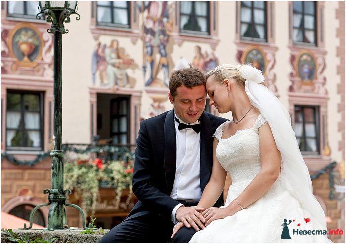 Жених и невеста сидят, прислонившись друг к другу, на фоне дома - фото 98533 Chanel№5