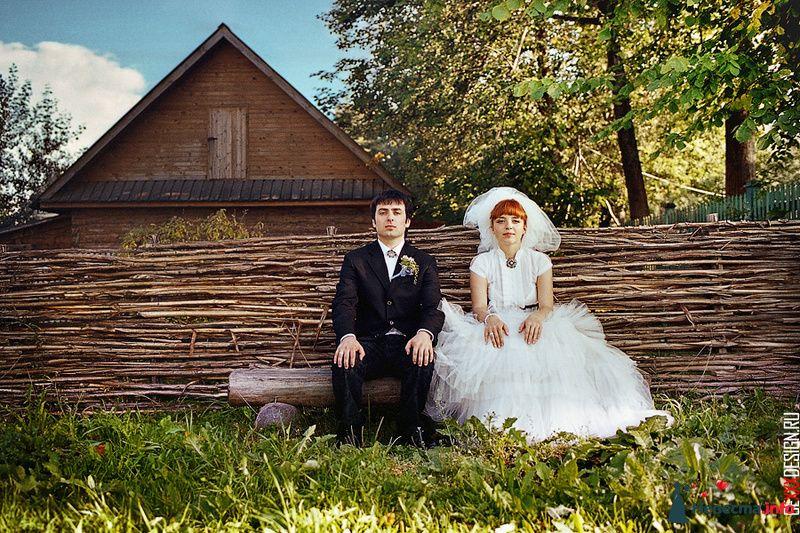Жених и невеста сидят на деревянной скамейке возле забора
