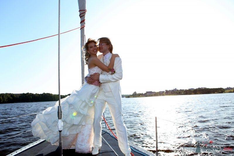 Жених и невеста стоят, прислонившись друг к другу, на яхте