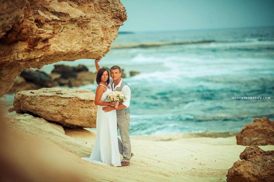 На песчаном пляже у скалы стоят молодожены, жених в серых брюках и жилетке обнимает за талию невесту в белом платье, в руке у нее - фото 2819061 Sunny Cyprus Wedding